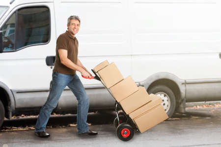 delivery box: A Smiling Delivery Man Pushing Parcels On Handtruck??In Front Of The Van Stock Photo