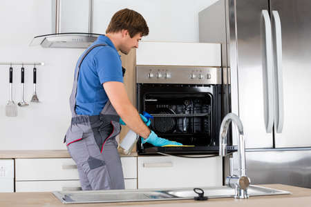 Happy Young Man In Overall Cleaning Oven With Rag And Bottle Spray