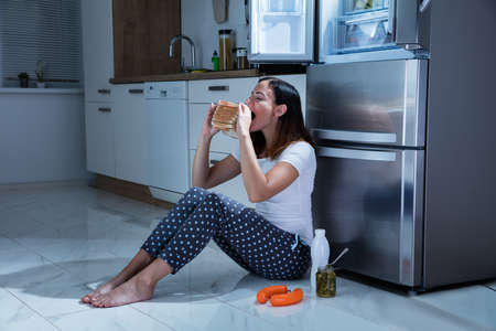 one woman: Young Woman Eating Sandwich With Jar Of Pickle While Sitting On Floor In Kitchen
