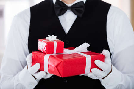 white gloves: Close-up Of Waiter Wearing White Gloves And Holding Christmas Gift