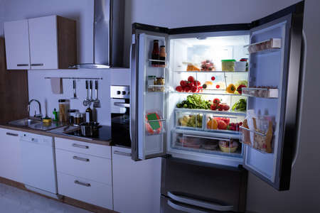 Open Refrigerator Full Of Healthy Items In Modern Kitchen Фото со стока