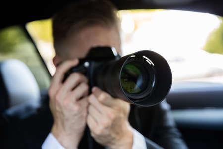 Haciendo detective privado que se sienta dentro del coche de Vigilancia de Trabajo fotografía con la cámara