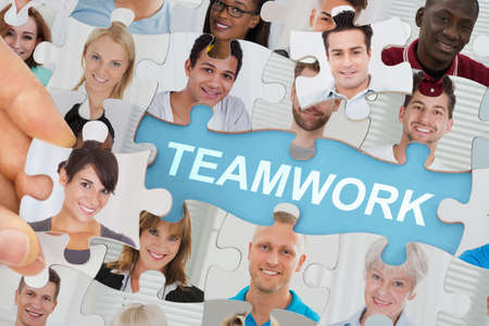 business puzzle: Teamwork Concept With Multicultural Business People Team On Jigsaw Puzzle Stock Photo