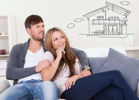 about: Young Thoughtful Couple Sitting On Sofa Thinking Of Getting Their Own House