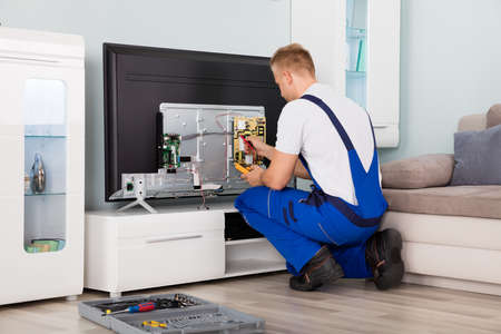 servicing: Young Male Electrician In Overall Checking Television