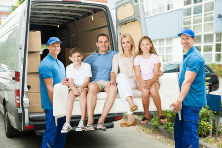Two Male Happy Furniture Movers Carrying Family On Sofa Out Of Truck Outside The House. Stock Photo