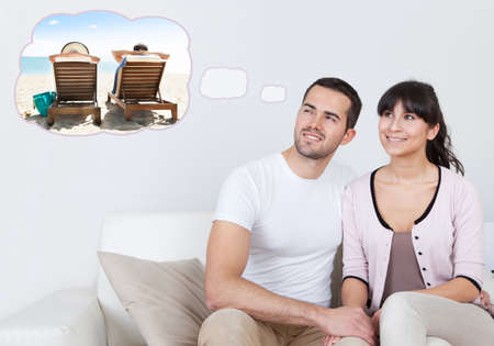 Young Happy Couple Sitting On Sofa Dreaming Of Spending Vacation Together On Beach At Home photo