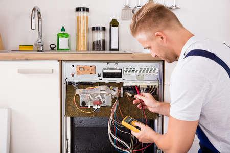 Young Male Techniker überprüfen Geschirrspüler mit Digitalmultimeter in der Küche