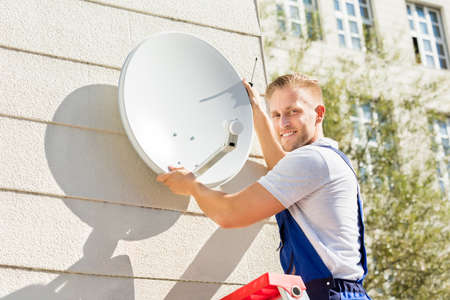 Young Man Fitting TV Satellite Dish To Wall Stock Photo