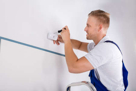 motion sensor: Male Electrician Installing Security System Door Sensor On Wall