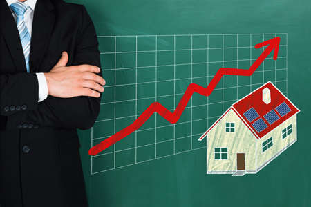 real estate growth: Close-up Of Businessperson Standing Beside Real Estate Growth Concept On Blackboard Stock Photo