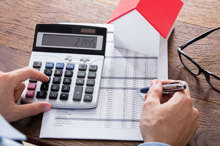 account executive: Close-up Of A Person Hand Calculating A Real Estate Property Tax On Wooden Desk Stock Photo