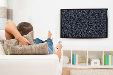 no signal: Man With Remote Control Relaxing On Couch In Front Of Television Showing No Signal At Home