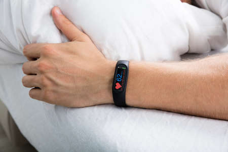 device: Fitness Activity Tracker With Heartbeat Rate On Mans Hand Over Bed