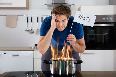 Worried Young Man Holding Help Flag With Utensil On Fire On Electric Stove At Home Reklamní fotografie