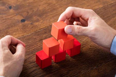 Nahaufnahme einer Person Hand Building Blocks auf Holz-Schreibtisch