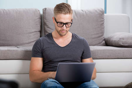 laptop home: Portrait Of A Man Using Laptop At Home