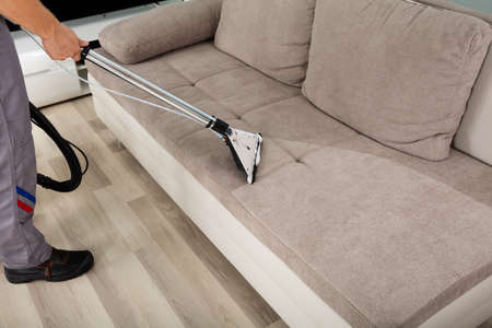 Young Male Worker Cleaning Sofa With Vacuum Cleaner