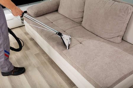 Junge männliche Arbeitnehmer Reinigung Sofa mit Staubsauger