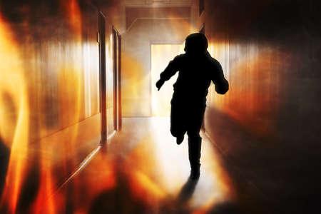 건물의 복도에서 화재 탈출하는 사람의 실루엣을 탈출