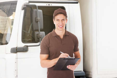 Portrait Of Smiling Delivery Man In Uniform Holding Clipboard By Truck photo