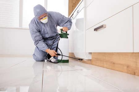 Exterminator In Workwear Spraying Pesticide With Sprayer Foto de archivo