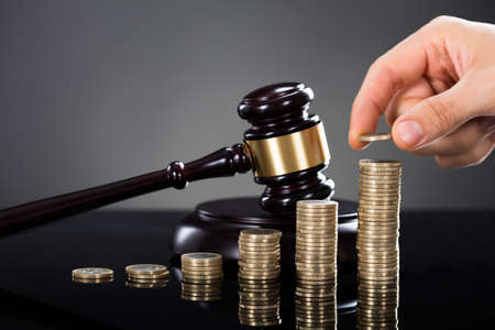 Close-up Of A Person Hand Stacking Coins In Front Of Mallet Over Gray Background Stock Photo