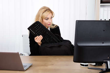 office supply: Businesswoman Stealing A Keyboard Secretly From Office Desk Stock Photo