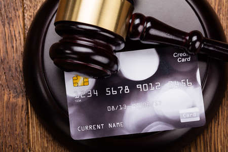 fraudster: High Angle View Of Credit Card On Wooden Gavel At Wooden Desk In Courtroom