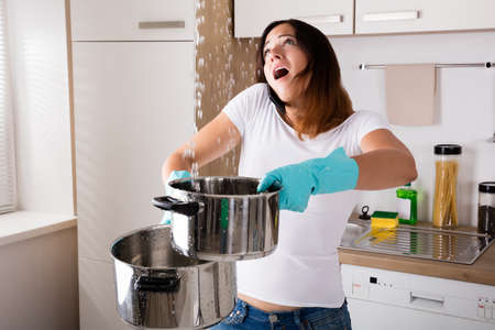 Shocked Woman Calling Plumber While Collecting Water Leaking From Ceiling Using Utensil