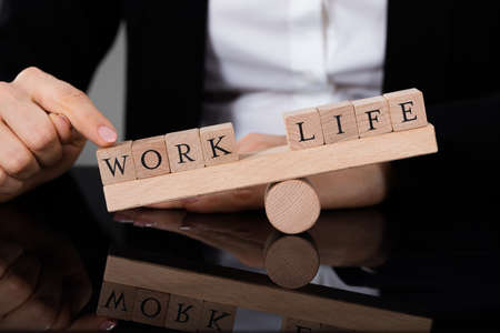 Close-up Of A Person Showing Imbalance Between Life And Work On Seesaw Stockfoto