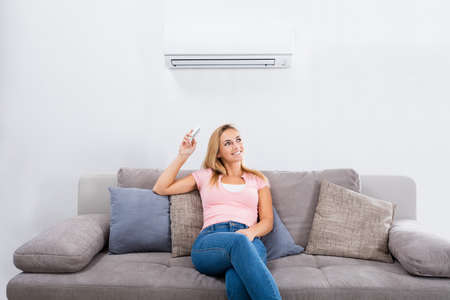 Young Happy Woman Sitting On Couch Operating Air Conditioner With Remote Control At Home