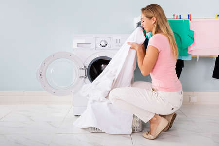 cleaned: Woman Smelling Cleaned Clothes Near The Electronic Washer At Laundry Room Stock Photo
