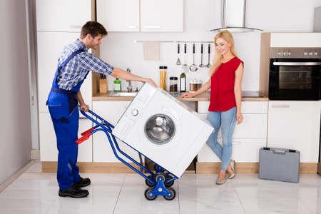 젊은 행복한 여자 남성 작업자 부엌에서 세탁기 운반에 대한 핸드 트럭을 사용하여 찾고