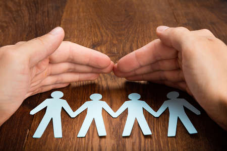equal to: Close-up Of Person Hand Protecting Human Figure Cutout On Wooden Desk Stock Photo