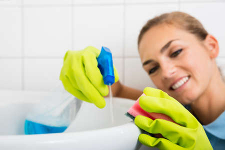 bathroom equipment: Close-up Of Smiling Woman Cleaning The Basin With Spray Bottle And Sponge In The Bathroom