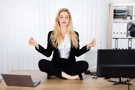 A Young Woman Doing Yoga While Sitting On Wooden Desk