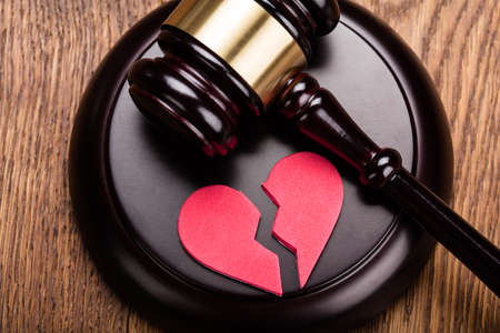 Red Broken Heart On Wooden Gavel At Wooden Desk