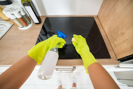 regular people: Cleaning Service Woman Hand Cleaning The Induction Stove In The Kitchen With Sponge