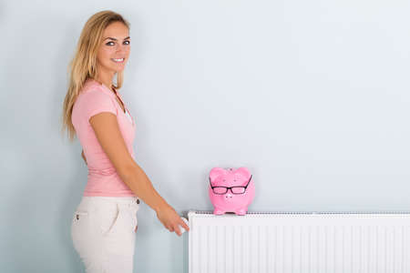 central bank: Smiling Young Woman Adjusting Thermostat To Reduce Heating To Save Money On Energy Bill