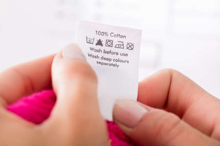 Close-up Of Person Reading The Clothing Label Showing Washing Instructions