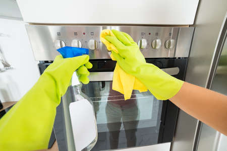 handglove: Woman Hand Wearing Glove Cleaning The Oven In The Kitchen At Home