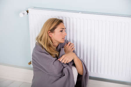 cold: Young Cold Woman Wrapped In Blanket Sitting Near Central Heating System At Home