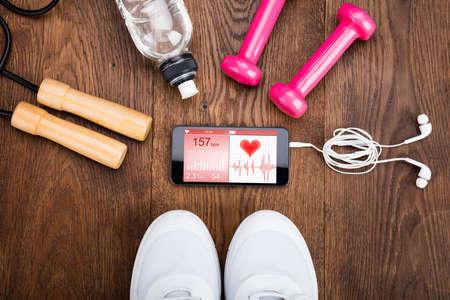 나무 바닥에 건강 응용 프로그램을 보여주는 휴대 전화와 운동 장비 스톡 콘텐츠