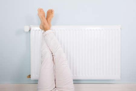Femme Réchauffer pieds sur radiateur blanc à la maison