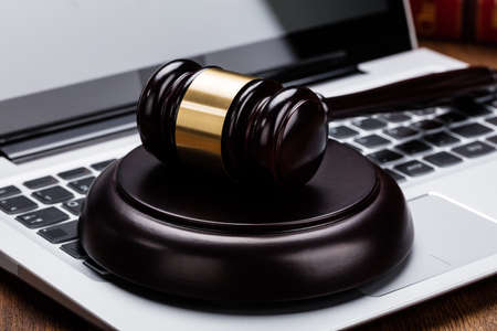golden rule: Close-up Of A Wooden Judge Gavel On Laptop Keyboard