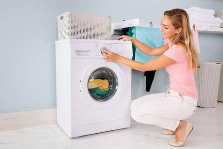 Jonge Glimlachende Vrouw Met Wasmachine Om Kleren In Wasruimte Schoonmaken Stockfoto