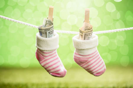 care allowance: Pair Of Baby Sock With Dollar Hanging On Rope Using Wooden Clip