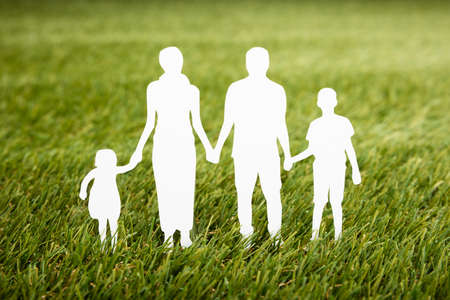 Close-up Of Family Papercut On Grassy Field