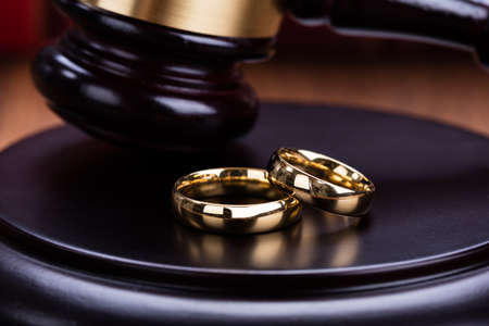 Close-up Of Wedding Rings Are Placed On Gavel In Courtroom Stock Photo